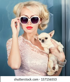 attractive woman in sunglasses with small dog in hand