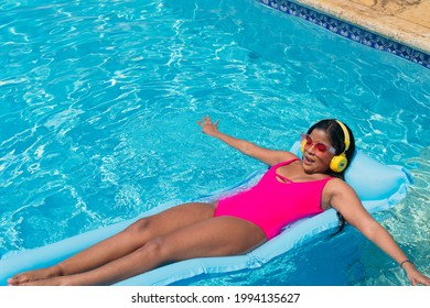 Attractive woman in swimwear stands in the sun listening to music with headphones on tropical vacation.