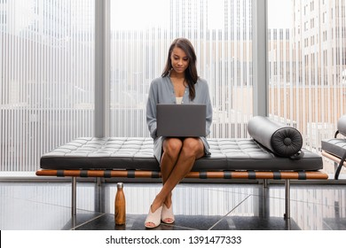 Attractive woman taking break from the office. Sitting on a bench and working on her laptop in an industrial lobby setting.