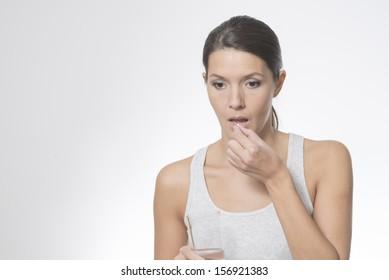 Attractive woman taking medication holding a glass of water in one hand as she slips a tablet or antibiotic into her mouth to treat an illness, or a painkiller or supplement