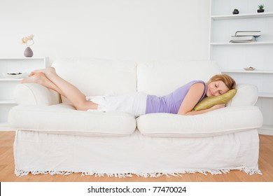 Attractive woman taking a rest lying on a sofa in the living room