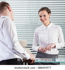 Attractive woman talking with her co-worker during work