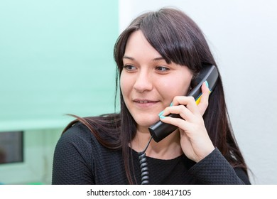 Attractive woman talking on phone in office