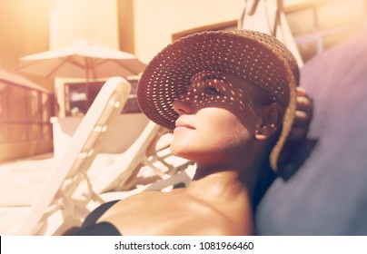Attractive woman tanning on the beach, lying down on sunbed and taking sun, nice female hides her face from the sun under a straw hat, summer vacation concept