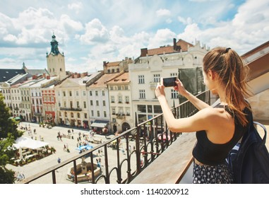 attractive woman tourist walking in the center of old city of Lviv with small blue backpack. woman admires the view of the cityscape from the rooftop with wonderful cloudy blue sky on background and