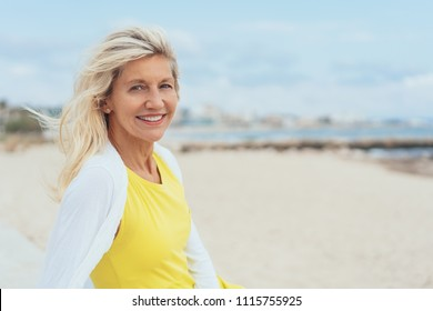Attractive woman with tousled hair on a windy beach turning to smile at the camera with copy space