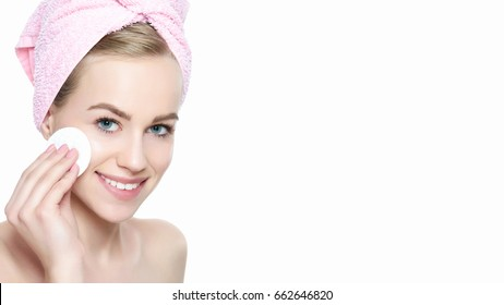 Attractive woman with towel in her hair removing make up. Smiling pretty girl with perfect complexion cleansing her face using soft cosmetic cotton pad. Isolated on white background with copy space.