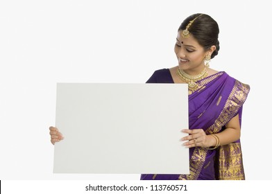 Attractive woman in traditional Assamese mekhla holding a blank placard and smiling