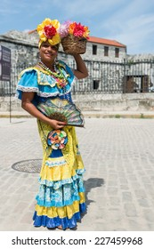 Attractive woman in traditional Cuban clothing posing at the street of Havana, Cuba