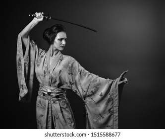 Attractive woman in traditional Japanese kimono with katana ( japanese sword). Young beautiful woman with perfect hair and makeup. black and white. Copy space.