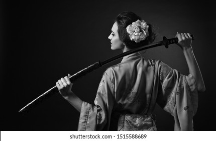 Attractive woman in traditional Japanese kimono with katana ( japanese sword). Young beautiful woman with perfect hair and makeup. black and white.