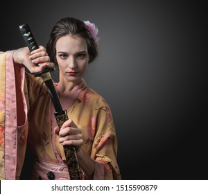 Attractive woman in traditional Japanese kimono with katana ( japanese sword). Young beautiful woman with perfect hair and makeup. Copy space.