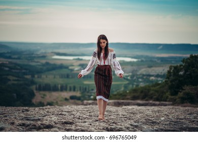 Attractive woman in traditional romanian costume on mountain green blurred background. Outdoor photo. Traditions and cultural diversity