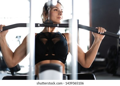 Attractive woman training in light modern gym. Beautiful muscular fit woman exercising building muscles
