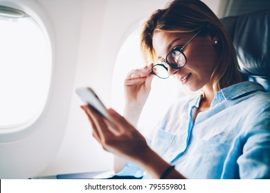 Attractive woman traveling by plane spending time during flight on reading news from networks on mobile, young female traveler browsing network news on phone for connecting internet on aircraft cabin