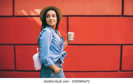 Attractive woman in trendy outfit walking around city street near publicity area with copy space area for advertising text, beautiful female tourist with coffee to go exploring world during vacations