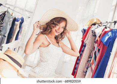 Attractive woman trying on a hat. Happy summer shopping.