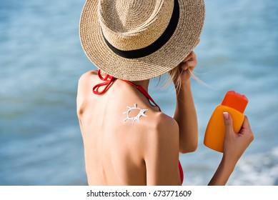 attractive woman use sunblock cream