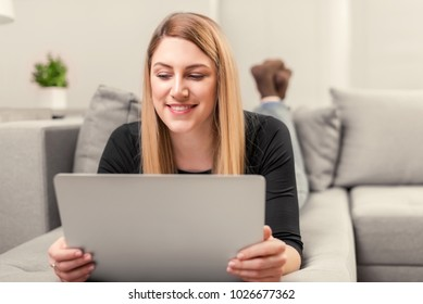Attractive woman using a laptop while lying on the sofa at home.