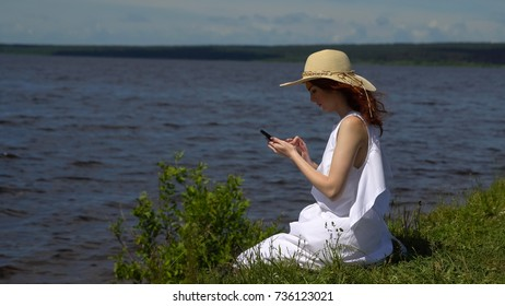Attractive woman using mobile phone on riverside, deep blue water on background