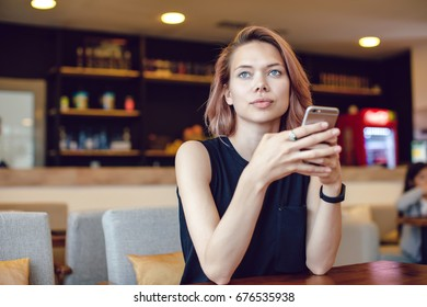 Attractive woman using smartphone in a cafe.