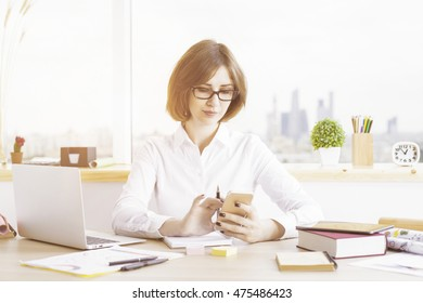 Attractive woman using smartphone at office desktop with various items