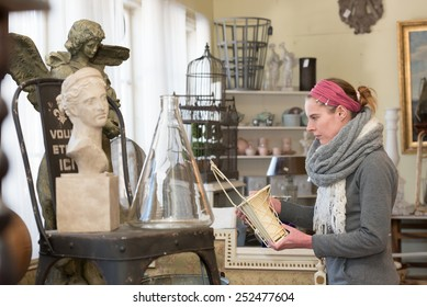 Attractive woman visiting an antique shop and looking for precious nice things