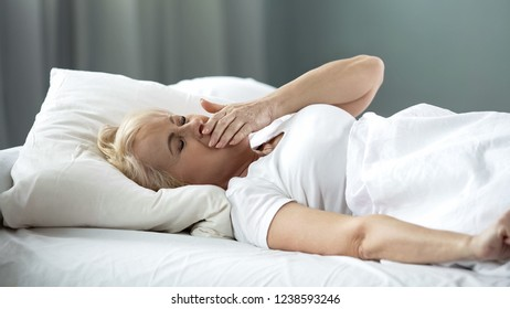 Attractive woman waking up, stretching hands and yawning, morning time, health