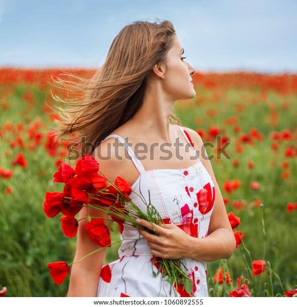 Attractive woman walking in a poppy field
