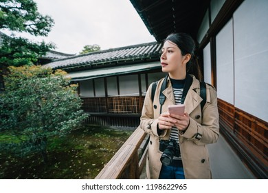 attractive woman walking through the garden while chatting with her friend on the cellphone. Self-guided trip concept with traveler reading online guidebook. Travel in Kyoto.