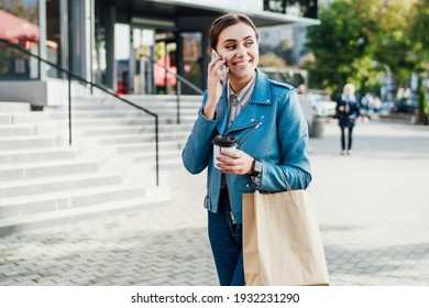 Attractive woman walks the streets of the city, speaks with a smile on the phone, shopping, lifestyle.