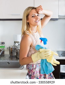 Attractive woman washing the kitchen top with a detergent