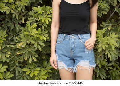 Attractive woman wearing back camisole and jean shorts on leave background.