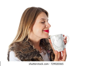 Attractive woman wearing fur coat, drinking hot tea on isolated background, fall time