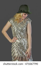 An attractive woman wearing a glamourous dress and a fedora