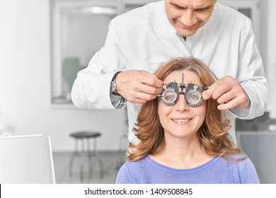 Attractive woman wearing glasses with lens for checking vision in clinic. Female adult smiling and looking at letters for testing sight in optical store. Concept of ophthalmology.