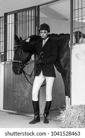 Attractive woman wearing jockey equipment posing near big black hourse. Indoor shot, sport and fashion concept.
