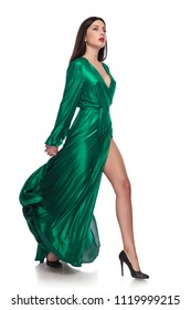 attractive woman wearing a long green dress walks to side on white background, full body picture