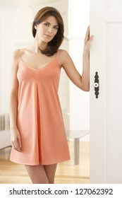 Attractive woman wearing a peach nightgown opening a white door. This photography was made with a top model and professional to reach this quality from a raw.