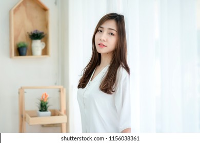 Attractive woman wearing sleeping suit standing alone. Asian young woman sleepless. Girl dreamy remembering great date.
