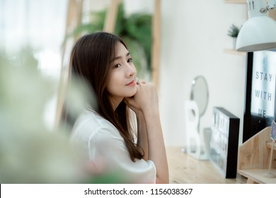 Attractive woman wearing sleeping suit sitting alone. Asian young woman sleepless. Girl dreamy remembering great date. Lady sitting and thinking of someone.