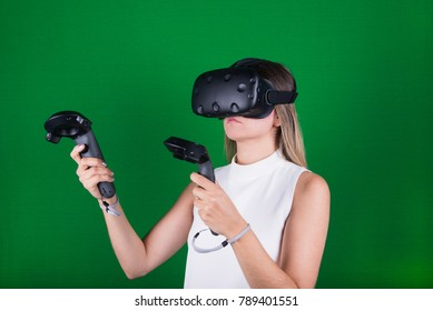 attractive woman wearing virtual reality headset with two handheld trackpads or controllers in green screen studio
