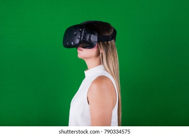 attractive woman wearing virtual reality headset and immersed into her experience in green screen studio