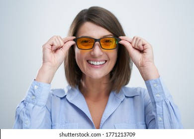 Attractive woman wearing yellow blue blocking glasses isolated over white background