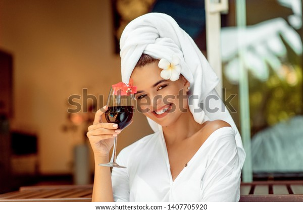 attractive woman in a white bathrobe and towel holding wine glass and  flower and smiling for the camera. Spa and resort concept