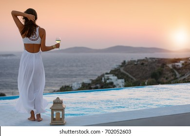 Attractive woman in white dress at the pool enjoys the sunset over the mediterranean sea with a glass of wine