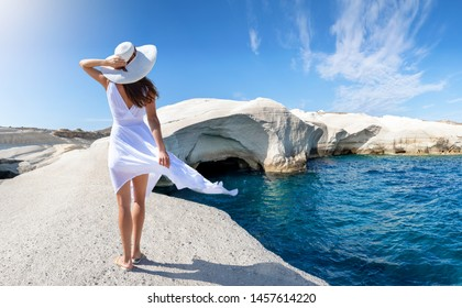Attractive woman in white dress walks on the lunar like landscape of Sarakiniko, volcanic rock formations on the island of Milos, Cyclades, Greece