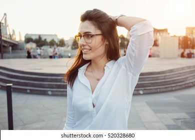 Attractive woman in white shirt is looking aside while standing on a city park background. A caucasian female with long brown hair is having fun outdoors.