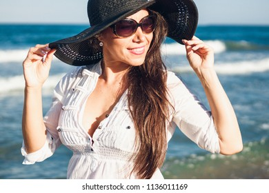 attractive woman with white shirt and pamela walks along the shore of the beach with glamor and style