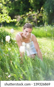 Attractive woman in white summer dress kneeling in grass in a charming garden and looks alluring
